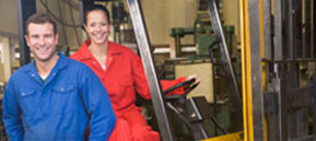 Smiling man and woman wearing coveralls working in a warehouse